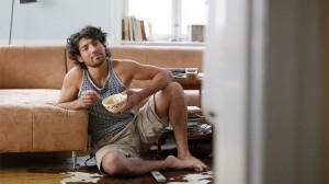 samsko življenje - moški sedi in je pred televizijo