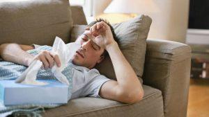 Moški z gripo v postelji